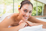 Beautiful smiling brunette lying on massage table with salt scrub on back