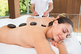 Happy friends lying on massage tables with hot stones on their backs