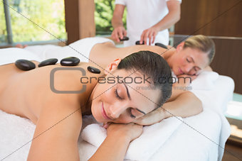 Calm friends lying on massage tables with hot stones on their backs