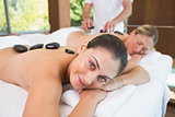 Pretty friends lying on massage tables with hot stones on their backs