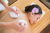 Smiling woman getting a back massage with herbal compresses