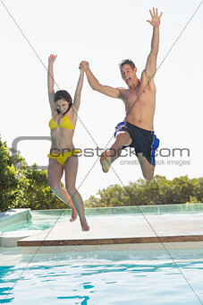 Excited couple jumping into swimming pool on holidays