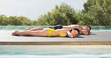 Gorgeous couple lying poolside on holidays