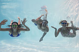 Smiling friends looking at camera underwater in swimming pool