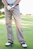 Lower half of golfer standing with club