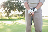 Mid section of golfer standing with club