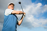 Golfer standing and swinging his club
