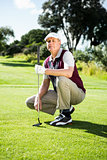 Golfer kneeling holding his golf club