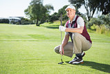 Confident golfer kneeling holding his golf club