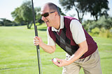 Excited golfer holding ball and club