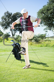Angry golfer trying to break his club