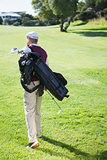 Golf player carrying his bag and walking