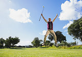 Excited golfer jumping up holding club