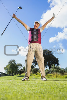 Excited golfer cheering and looking at camera