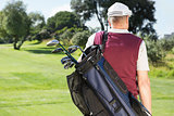 Golfer carrying his golf bag
