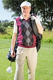 Golfer carrying his golf bag smiling at camera