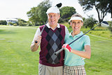 Golfing couple smiling at camera