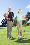 Golfing couple standing and looking around