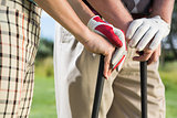 Golfing couple standing holding their clubs