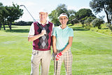 Golfing couple standing smiling at camera