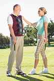 Golfing couple standing smiling at each other
