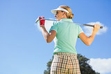 Female golfer standing holding her club