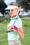 Female golfer standing holding her club smiling at camera