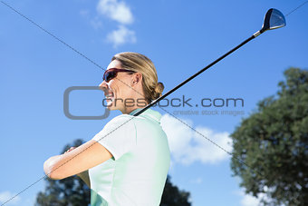Female golfer standing holding her club smiling