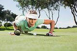 Female golfer blowing her ball on putting green