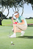Female golfer watching her ball on putting green