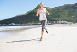 Pretty blonde jogging on the beach