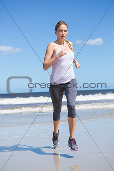 Focused fit blonde jogging on the beach