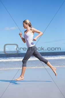 Focused fit blonde jogging on the beach barefoot