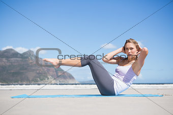 Focused fit blonde doing yoga on the beach