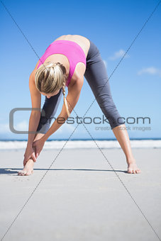 Focused fit blonde warming up on the beach