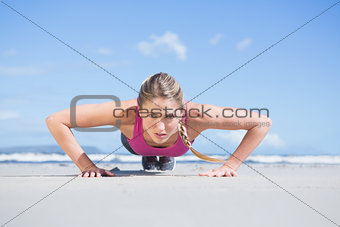 Fit blonde in plank position on the beach