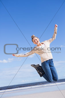 Pretty blonde in jeans jumping and smiling at camera