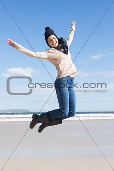 Pretty blonde in jeans leaping on the beach