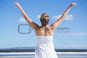 Pretty blonde standing with arms outstretched on the beach