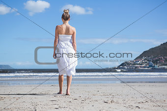 Blonde in white dress walking on the beach