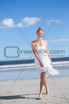 Blonde in white dress walking on the beach smiling at camera