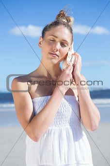 Pretty blonde in white dress listening to conch on the beach
