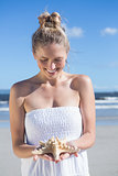 Pretty blonde in white dress holding starfish on the beach