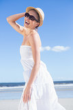 Pretty blonde in white dress and sunhat on the beach