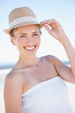 Pretty smiling blonde on the beach wearing straw hat