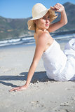 Content blonde in white dress sitting on the beach looking to camera