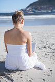 Content blonde in white dress sitting on the beach reading book