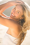 Blonde in white dress smiling at camera on the beach