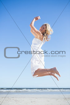 Blonde in white dress smiling at camera and leaping on the beach