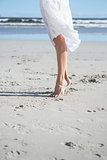 Woman in white dress stepping on the beach